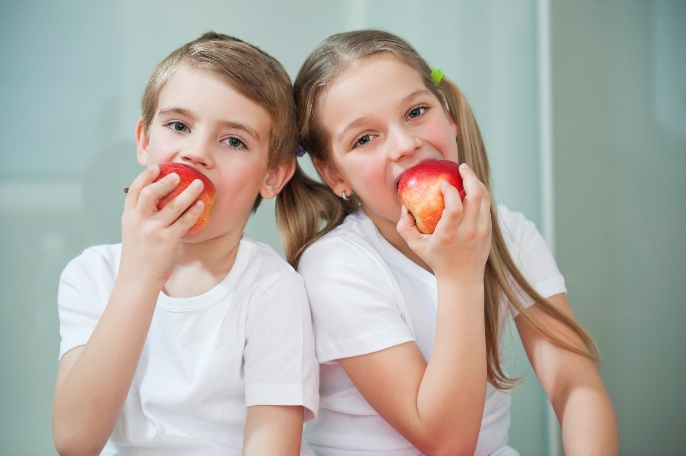 Girl and boy in white eating apples