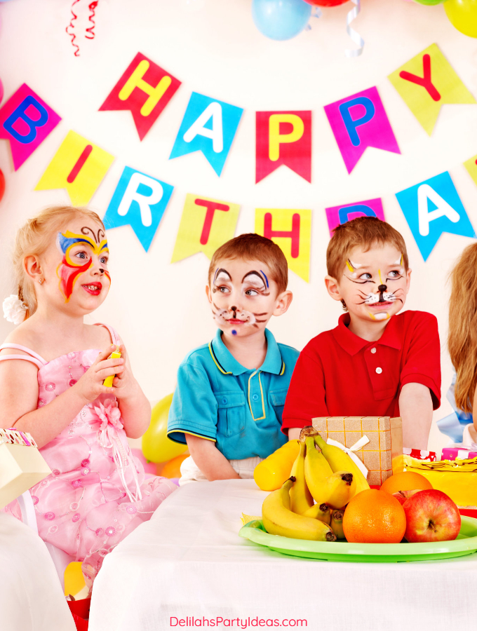 3 children with their faces painted at a party with banner that says Happy Birthday
