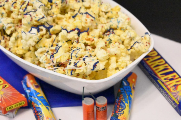 Bowl of firecracker popcorn and firecrackers in boxes as display around the white bowl