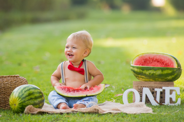 Birthday boy on garden with watermelon on his lap and he is wearing a red bow tie