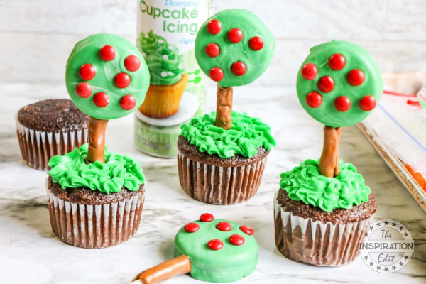 Chocolate cupcakes with green icing and a tree looking oreo coated in green icing and red chocolate drops