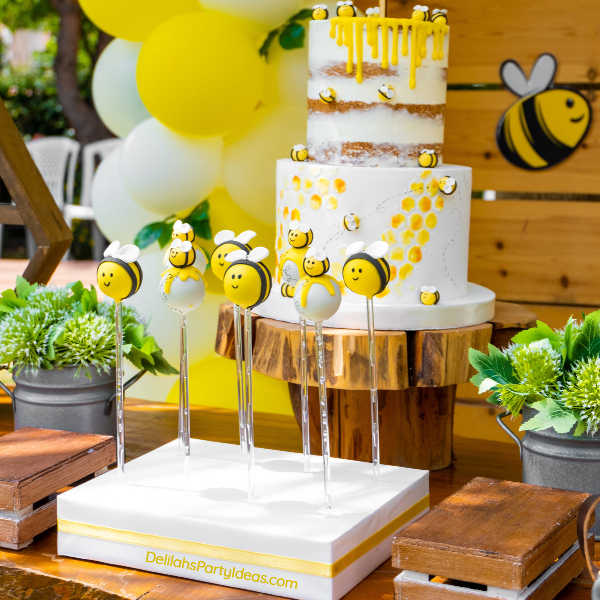 White cake with sugar bumble bees, honey and honeycomb looking icing and honey bee cake pops with yellow and white balloons in the background