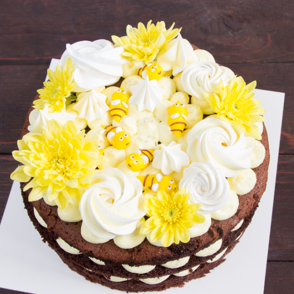 Cake with sugar flowers and real flowers in white and yellow with little icing bumble bees