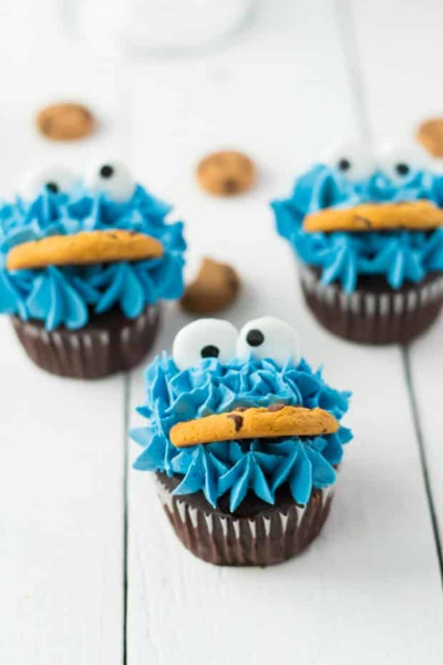 3 cupcakes that look like cookie monster from sesame street, blue icing googly eyes and cookie in mouth
