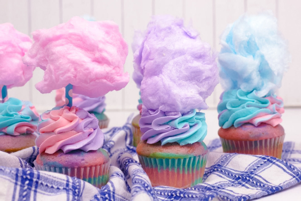 Pastel colored cupcakes with cotton candy on the top of the icing
