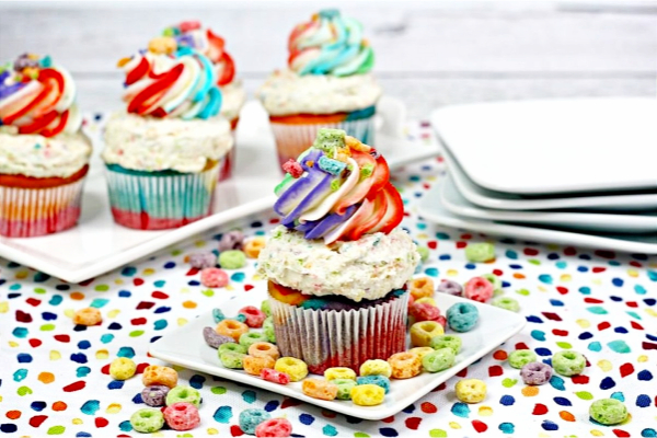 A plate of Cupcakes with Rainbow colored icing and fruit looks on the plate