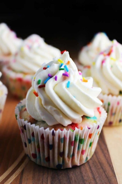 Cute homemade cupcake with icing and colorful sprinkles on it