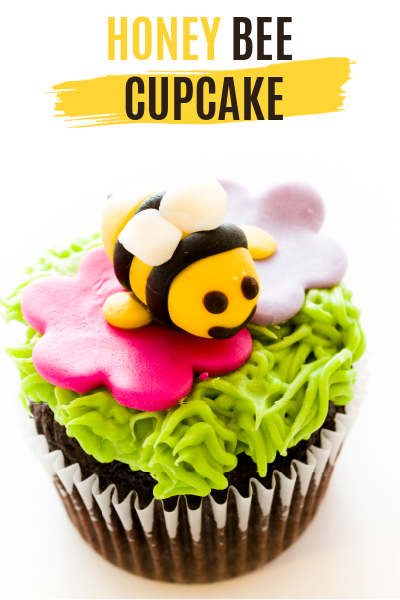 Cute little chocolate cupcake with green icing pink flower and a honey bee made of fondant.