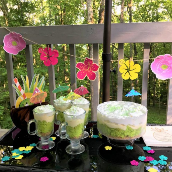 summer party table with flower decorations and key lime coconut parfaits in glasses and trifle bowl