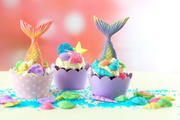 3 gorgeous Mermaid cupcakes with icing and mermaid tails made of candy sticking out of top