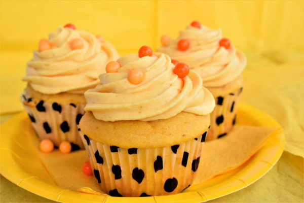 3 Pumpkin cupcakes with icing and orange balls on top