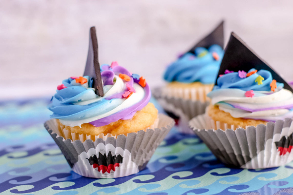 2 cupcakes in silver shark foils and cupcakes with icing and black triangle fondant as fin