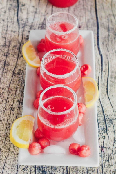 3 glasses of watermelon agua fresca on a white platter with lemons