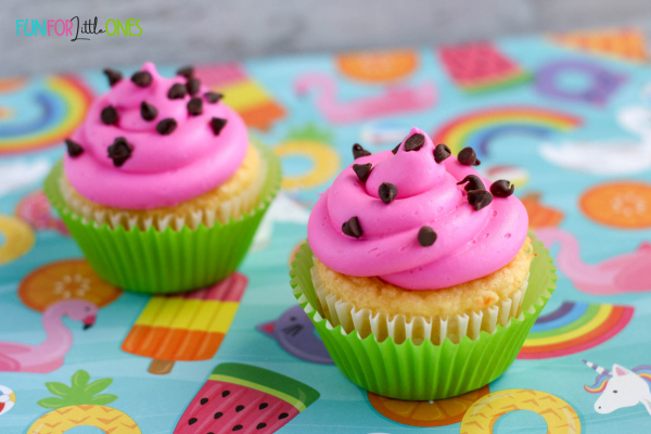 Pretty cupcakes with pink icing and green foil cupcake liners and choc chips on icing looks like a watermelon