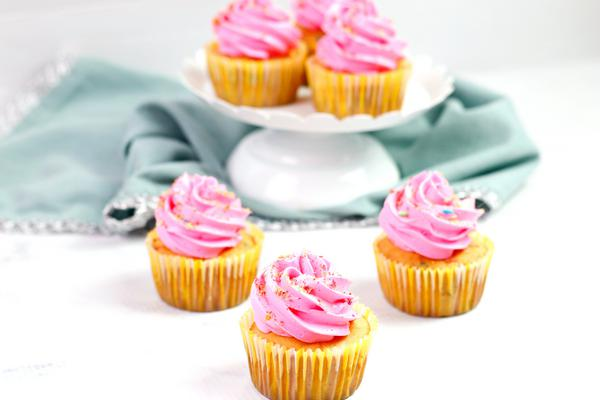 Pretty in pink cupcakes on a white table with a cake stand and 3 more cupcakes