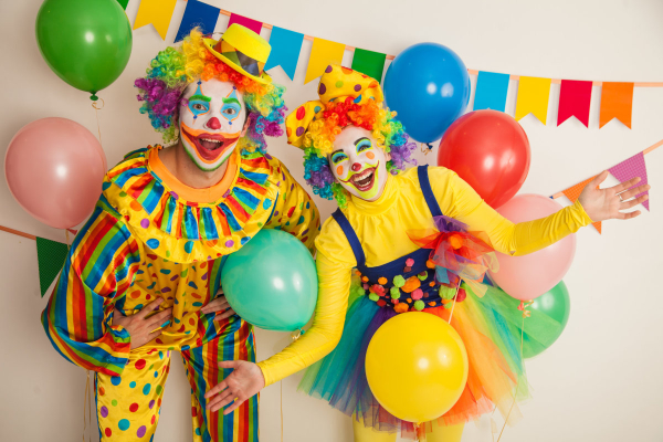 two party clowns with balloons and party banner