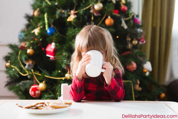 Child in front of Christmas Tree drinking hot chocolate