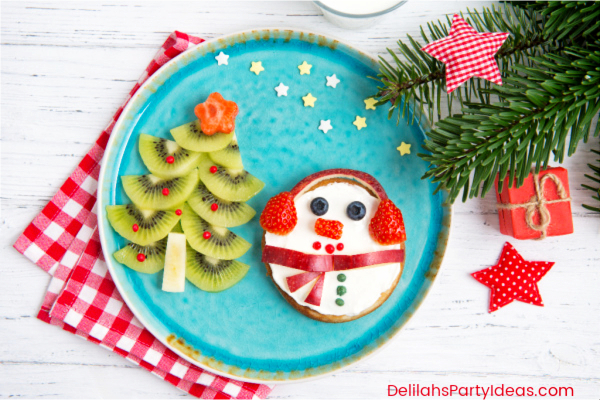 Plate with Kiwi fruit made in to a Christmas tree and an apple snowman