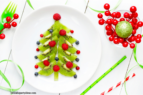 Kiwi fruit strawberries and blueberries arranged on a white plate like a Christmas tree