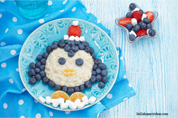 Blue plate with porridge and fruit shaped like a penguin