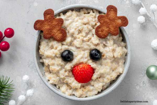 Bowl of porridge with cookie ears, strawberry nose and blueberry eyes that looks like Rudolph the red nosed reindeer.