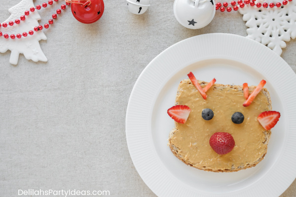 Peanut butter on toast with strawberries and blueberries and looks like Rudolph the red nosed Reindeer