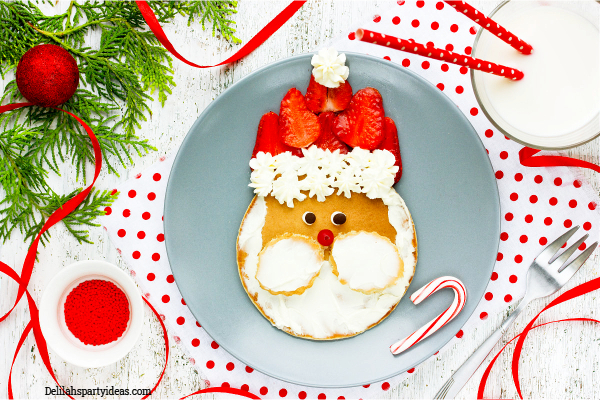 Grey plate with pancakes, strawberries and cream in the shape of Santa's face with white cream beard