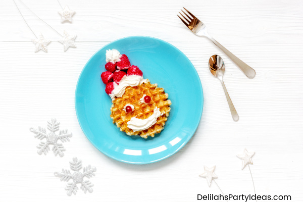 Blue plate with a waffle and strawberries as a hat and cream as beard