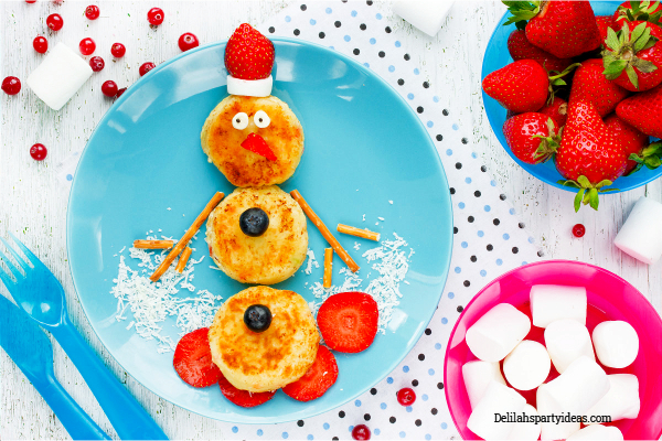 Blue plate with pancakes in the shape of a snowman with pretzel sticks as arms, strawberry and marshmallow as a hat and blueberry buttons