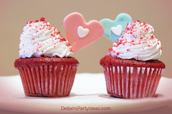 2 red velvet cupcakes one with pink heart and one with blue heart