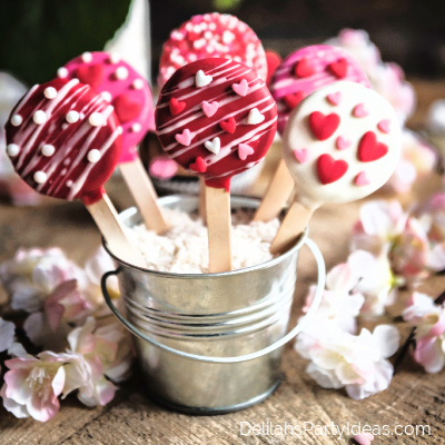 Oreo cookies on sticks covered in chocolate and heart sprinkles
