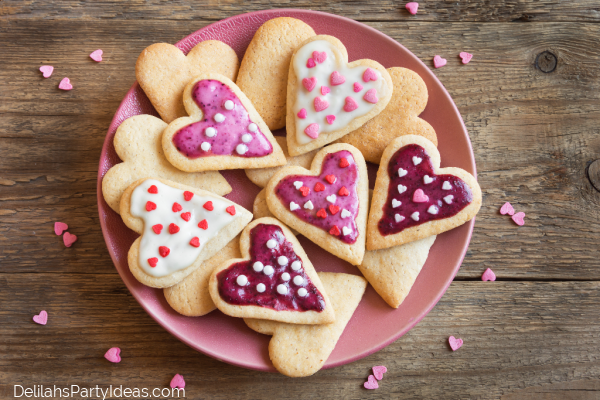 Plate of iced heart shaped cookies and wooden background
