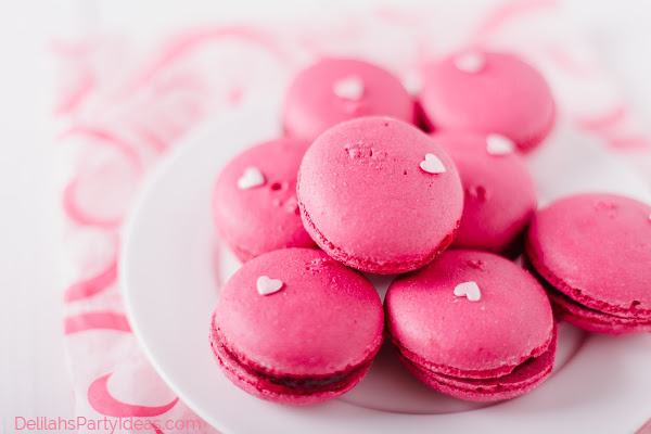Plate of french hot pink macaroons and sugar hearts decoration on top.