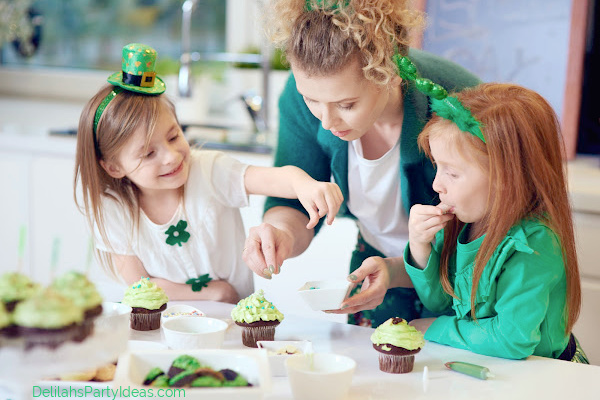 Two young girls with Mom making St Patrick's day Cupcakes