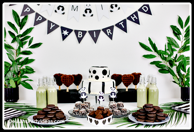 Party Table with panda cake and greenery and Happy Birthday banner